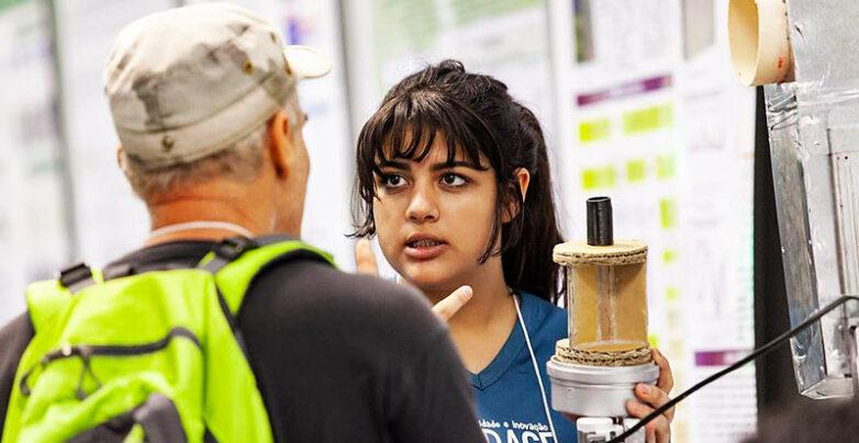 Estudante no estande da FEBRACE apresentando seu projeto
